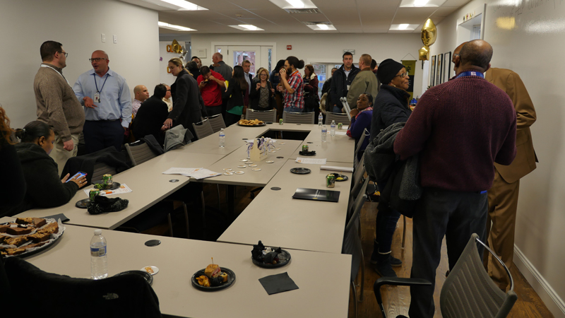 Picture of a crowded room talking and socializing